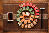 Japanese sushi, food art. Great set of fresh rolls served as colorful spiral on brown straw mat, flat lay. Luxury restaurant menu photo, traditional oriental cuisine.