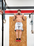 Bodybuilder doing pull ups in gym