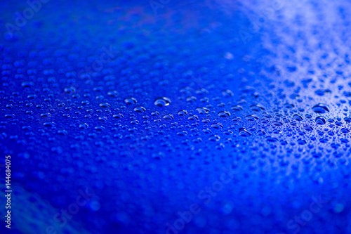 Leinwanddruck Bild closeup to water drops on glass with lighting background