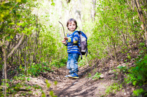 A child walks through the woods.