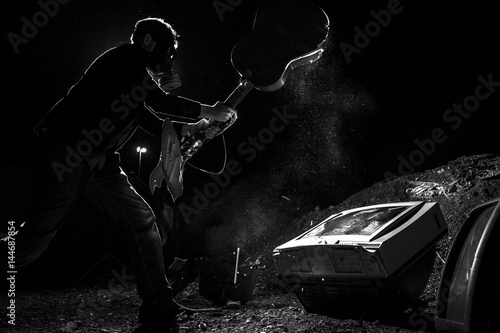 masked man smashing guitar