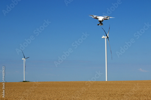 drone flying over wheat field with wind turbine summer season