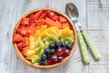 Breakfast oatmeal for kids topped with rainbow fruits © azurita