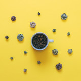 coffee beans in white Cup among the artificial roses on a yellow background. morning creative concept