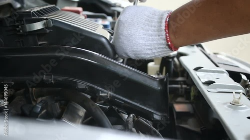Hands of man using fix wrench to repair car engine