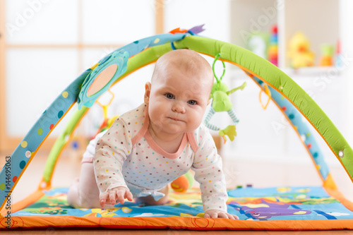 Poster Closeup of seven months baby girl crawling on colorful playmat