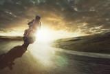 Motorrad fährt  durch eine Kurve bei Sonnenuntergang - 144703013