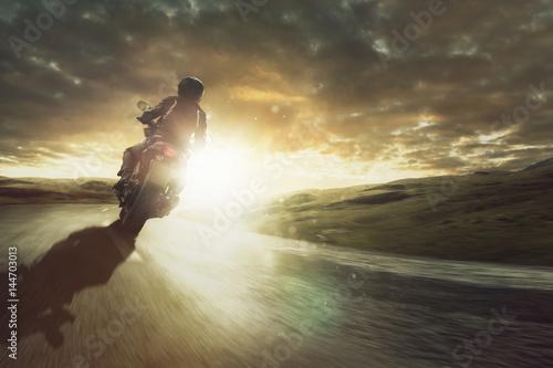 Motorrad fährt durch eine Kurve bei Sonnenuntergang