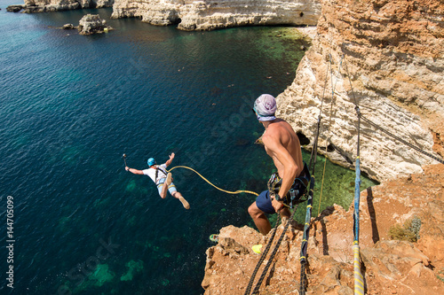 Rope jumping off a cliff with a rope in the water. The ocean. Sea. Mountain.