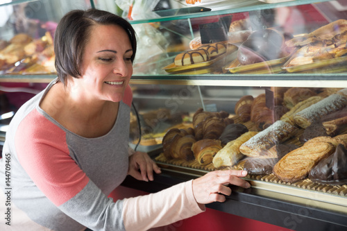Нарру woman looking into the pastry Poster