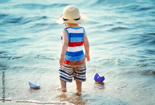 Poster little boy playing at the beach in straw hat