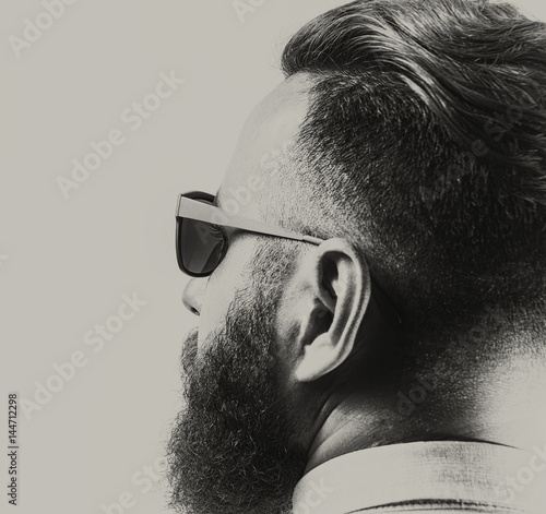 Portrait of a bearded man in sunglasses, with a stylish haircut. Black and white. - 144712298