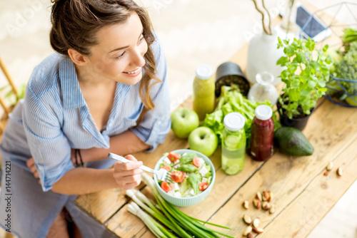 Młoda i szczęśliwa kobieta je zdrowego sałatkowego obsiadanie na stole z zielonymi świeżymi składnikami indoors