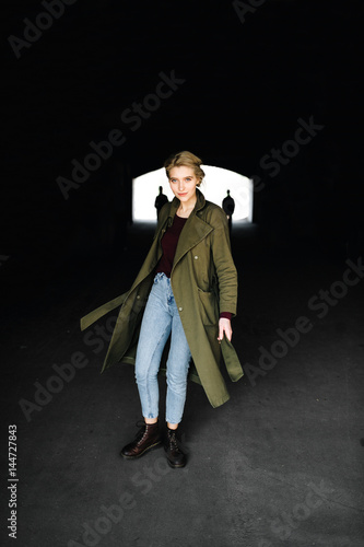 Beautiful and attractive young blonde actress celebrity girl in stylish coat and hipster boots escaping from dark tunnel with two extraterrestrial invaders on background Poster