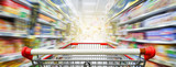 Supermarket aisle with empty red shopping cart - 144740825