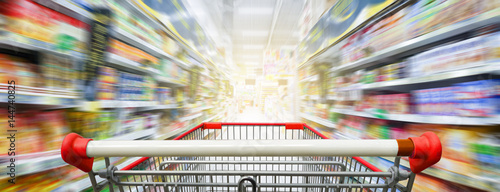 Supermarket aisle with empty red shopping cart