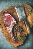 Dry aged raw beef rib eye steak with bone, butcher meat chopping knife and spices in bowls on rustic wooden board over grey concrete background, top view, vertical composition
