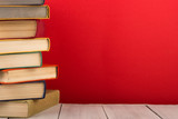 education and wisdom concept - books on wooden table, color background