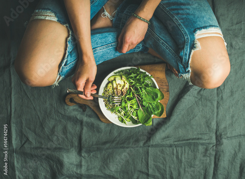 Green vegan breakfast meal in bowl with spinach, arugula, avocado, seeds and sprouts. Girl in jeans holding fork with knees and hands visible, top view, copy space. Clean eating, detox food concept