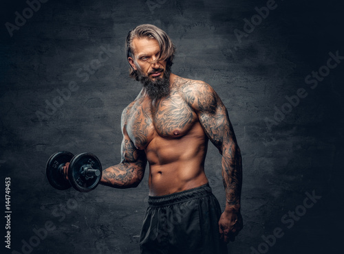 Tattooed male doing a biceps workout with dumbbell over dark grey background.