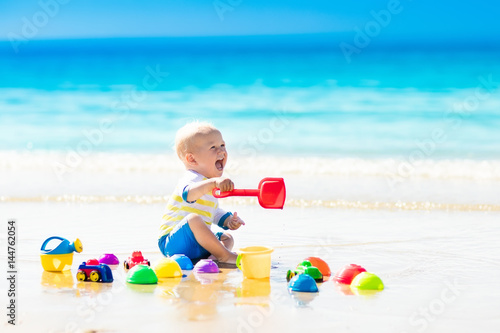 Baby playing on tropical beach digging in sand Poster