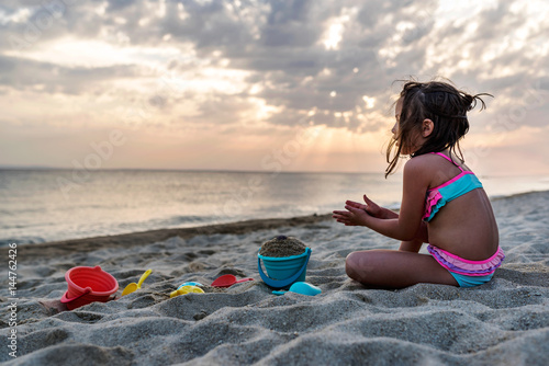 Little girl playing in the sand by the sea in the sunset Poster