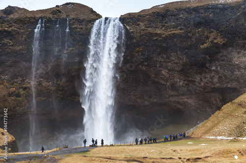 Tourists walk near Seljalandfoss waterfall - 144773642