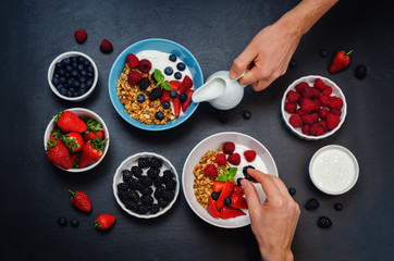 Male hands with healthy breakfast with granola, greek yogurt, berries and milk
