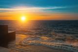 Stunning sunset on the sea a stone embankment.