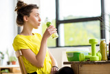 Fototapeta Young sports woman in yellow t-shirt drinking water with mint and cucumber. Detox concept