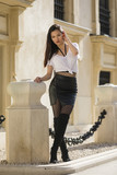 Beautiful Asian girl with skirt and boots on street