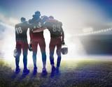The three american football players on on stadium background