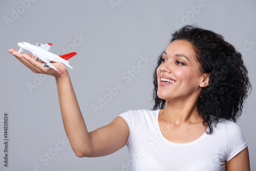 Plakat Closeup portrait of happy beautiful woman launching airplane model