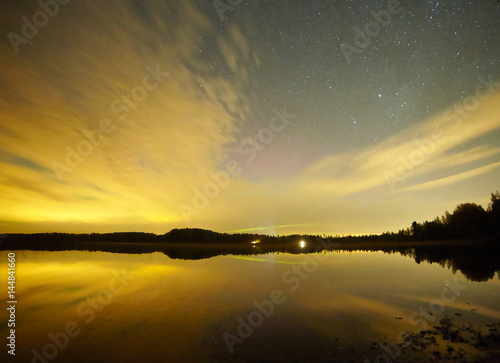 Stars and sunset in Finland. Reflection of the forest skyline in the calm water of a lake.