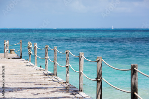 Długi drewniany molo i turkusowa woda morze karaibskie.