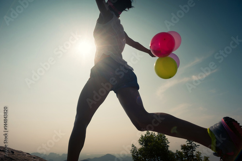Poster asian woman running on mountain top with balloons
