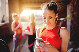 Fototapety Beautiful young woman listening music fitness training workout. Group of fitness people behind preparing for training.