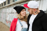 A young HipHop styled couple near the wall graffiti