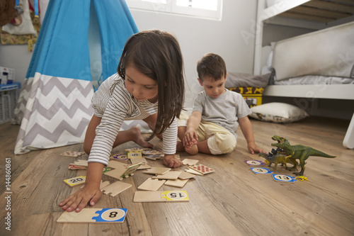 Plagát Two Children Playing Number Puzzle Game Together In Playroom