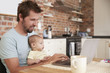 Father Working From Home On Laptop With Baby Son