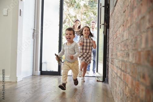 Leinwandbild Motiv Excited Children Arriving Home With Parents