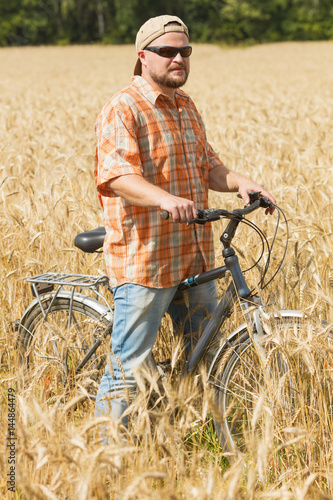 Poster Traveller in cap and sunglasses with a bicycle at the field