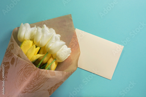 Yellow and white tulips with envelope in wrapping paper on a light turquoise background