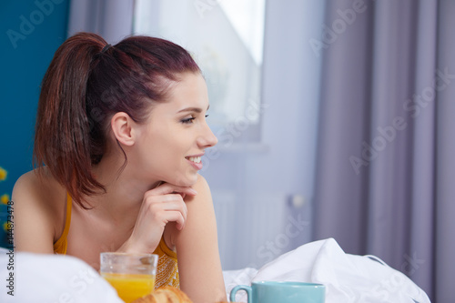Attractive woman eating cereals sitting on bed at home