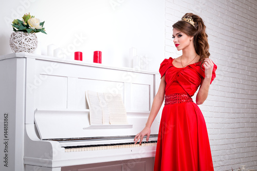 Plakat Beautiful elegant girl in a long red dress and shoes is standing next to the pia