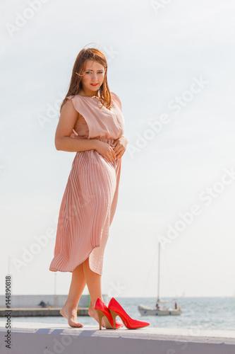 Plakat Woman wearing long light pink dress on jetty