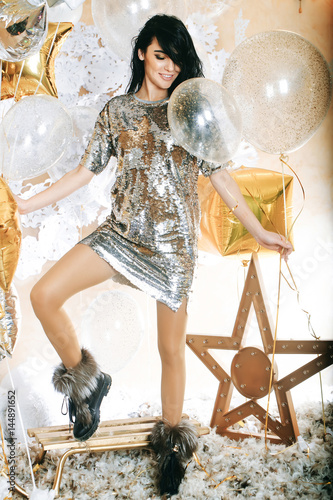 Poster sexy woman in silver sequins dress with festive balloons, sledge