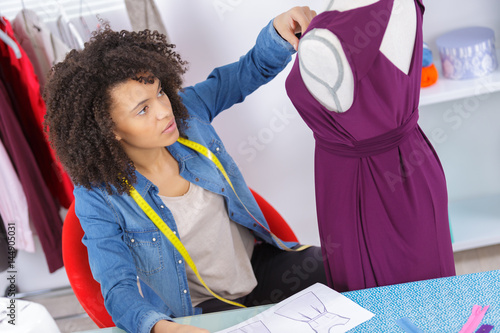 woman tailor working on new dress Poster