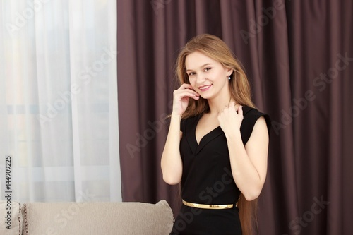 Plakat Young girl with black dress against curtains