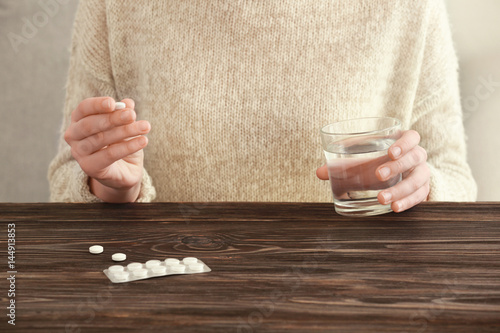 Young woman with pills and glass of water at home, closeup